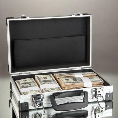 Suitcase with 100 dollar bills on grey background photo