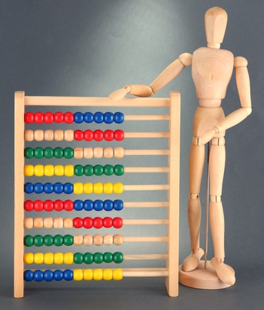Bright toy abacus and wooden dummy, on grey background Stock Photo - 17515113
