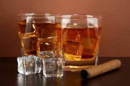 hard liquor: Glasses of whiskey and cigar on brown background
