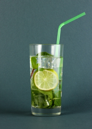 Glass of water with ice, mint and lime on grey background Stock Photo - 17518413
