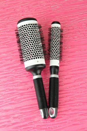 Two black combs on color background photo
