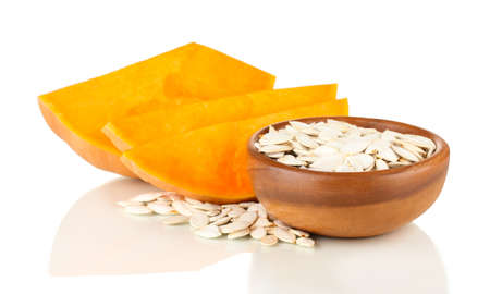 Pumpkin seeds  in wooden bowl isolated on the white photo