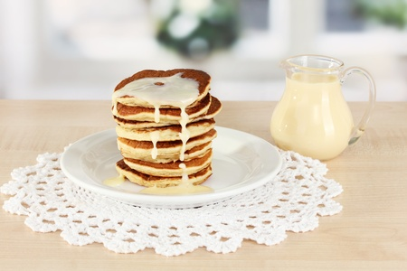 maslen: Sweet pancakes on plate with condensed milk on table in kitchen Stock Photo