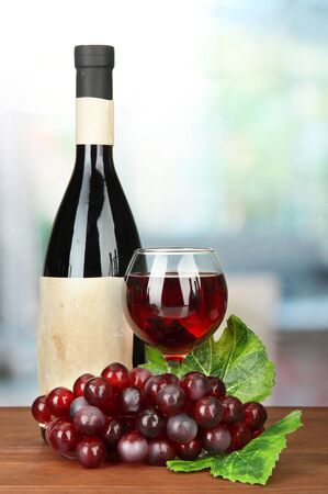 Composition of wine bottle, glass and  grape, on bright background Stock Photo - 17515125