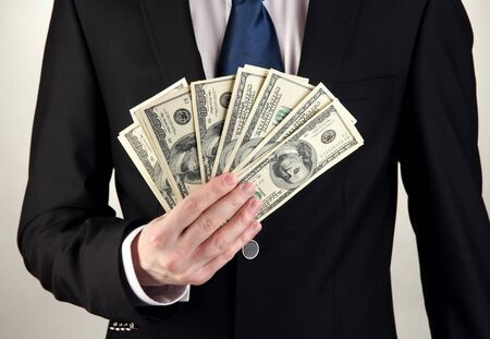 Business man holds lot of money on grey background Stock Photo - 17515288