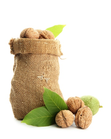 walnuts with green leaves in  burlap bag, isolated on white Stock Photo
