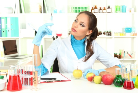 Young female scientist injecting GMO into   apple in  laboratory  photo