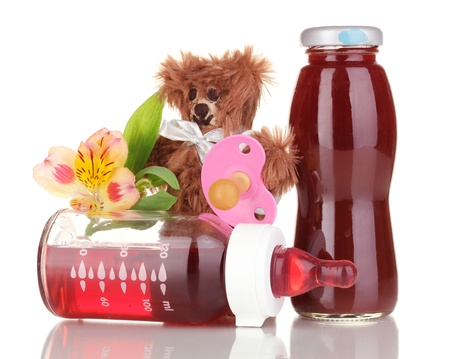 Baby bottle with fresh juice and teddy bear isolated on white photo