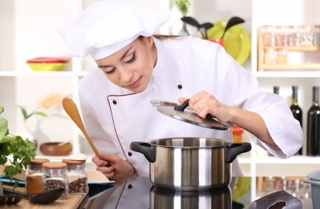 culinary skills: Young woman chef cooking in kitchen