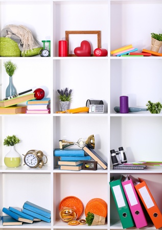 Beautiful white shelves with scattered different home related objects photo