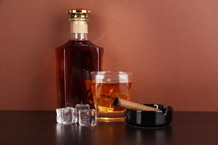Bottle and Glass of whiskey and cigar on brown background photo