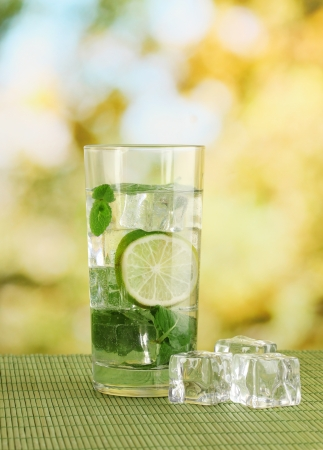 Glass of water with ice, mint and lime on table on bright background photo