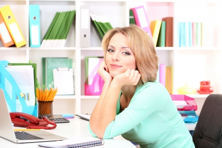 Young beautiful business woman in office at her workplace Stock Photo - 21537905