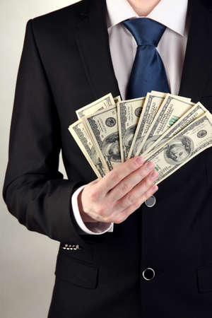 Business man holds lot of money on grey background Stock Photo - 17526031