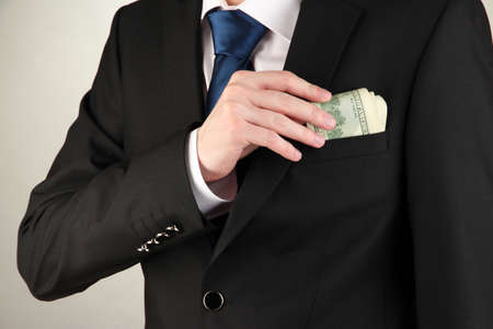 Business man hiding money in pocket on grey background Stock Photo - 17525978