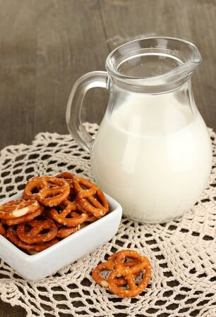 Tasty pretzels in white bowl and milk jug on wooden table close-up Stock Photo - 17526517