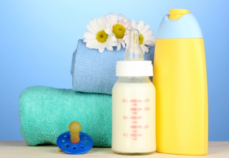 Baby bottle of milk and shampoo near towels on blue background photo