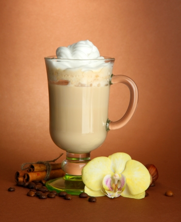 Fragrant coffee latte in glass cup with spices, on brown background photo