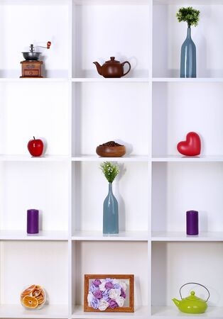 Beautiful white shelves with different home related objects photo