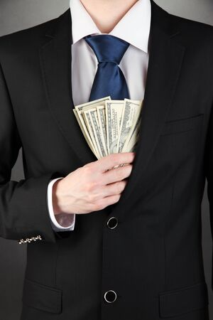 Business man hiding money in pocket on black background Stock Photo - 17526476