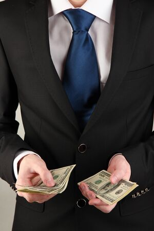 Business man counts money on grey background photo