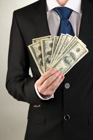 Business man holds lot of money on grey background Stock Photo - 17526521