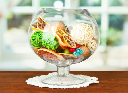 Dried oranges, wicker balls and other home decorations in glass bowl, on bright background Stock Photo
