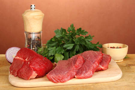 microelements: Raw beef meat with spices on wooden table on brown background