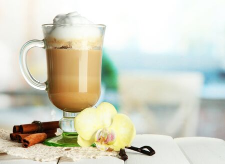 Fragrant coffee latte in glass cup with spices, on wooden table photo