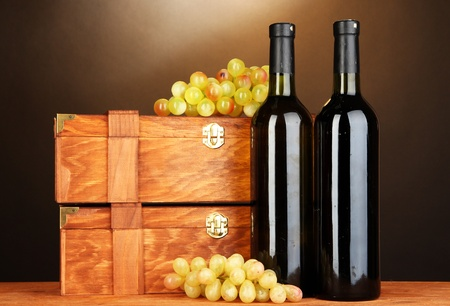 Wooden cases with wine bottles on wooden table on brown background Stock Photo - 17548311