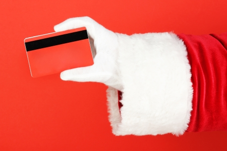 Santa Claus hand holding red credit card on red background Stock Photo - 17529283
