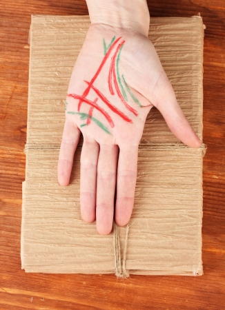 Chiromancy.Color contours on palm, on wooden background Stock Photo - 17548486
