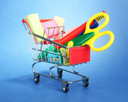 trolley with school equipment on blue background photo