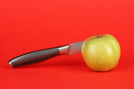 Green apple and knife on red background