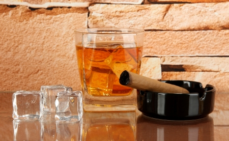 Glass of whiskey and cigar on brick wall background photo