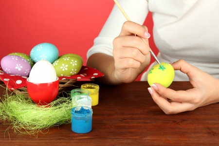 Young woman painting Easter eggs, on color background Stock Photo - 17548415