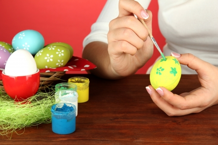 Young woman painting Easter eggs, on color background Stock Photo - 17548423