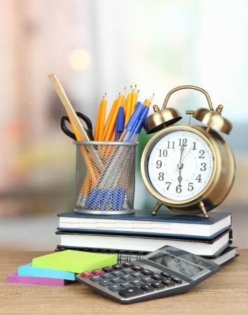 School supplies with clock on wooden table photo