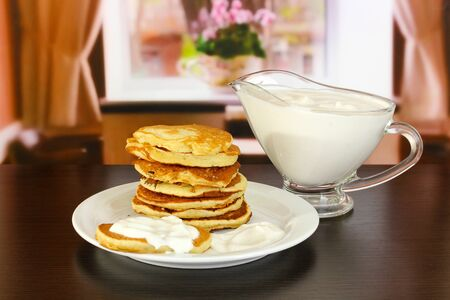 Sweet pancakes on plate with sour cream on table in room Stock Photo - 17548334
