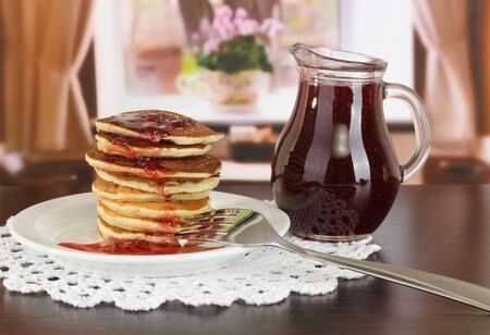 Sweet pancakes on plate with jam on table in room Stock Photo - 17548412