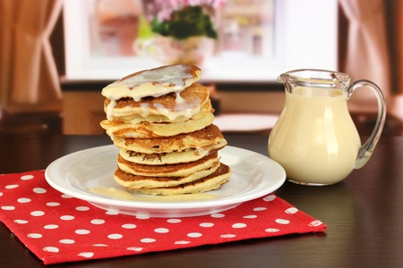 Sweet pancakes on plate with condensed milk on table in room Stock Photo - 17548425