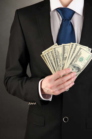 Business man holds lot of money on black background Stock Photo - 17548330