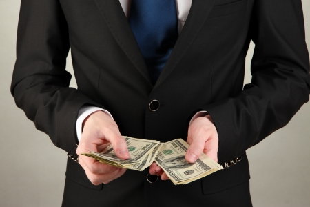 Business man counts money on grey background Stock Photo - 17529258