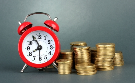 Alarm clock with coins on grey background Stock Photo - 17548216