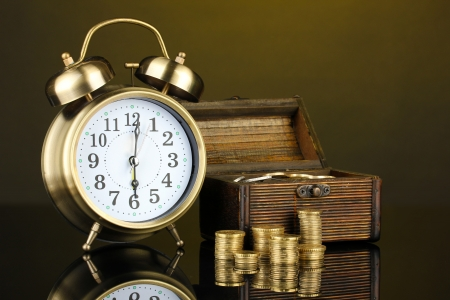 Alarm clock with coins in chest on dark background Stock Photo - 17531251