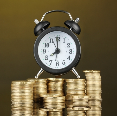 Alarm clock with coins on dark background Stock Photo - 17548197