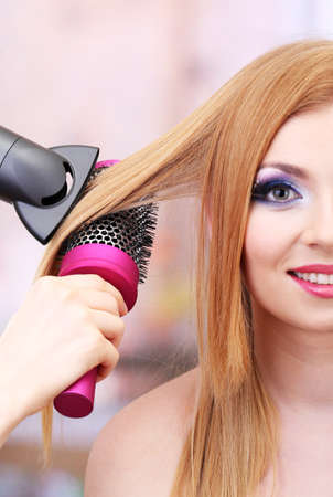 Beautiful woman and hands with hairdryer in beauty salon photo