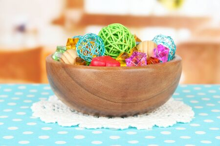 Dried oranges, wicker balls and other home decorations in wooden bowl, on bright background photo