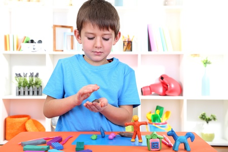 sculp: Cute little boy moulds from plasticine on table