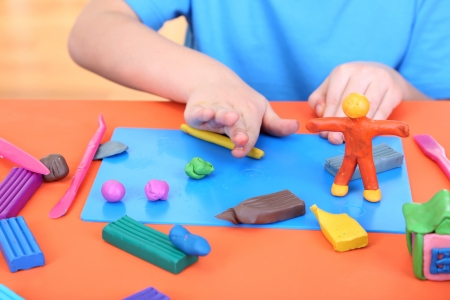 Child moulds from plasticine on table Stock Photo - 17529302